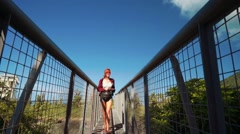 Young woman with waist bag and camera walking on metal net bridge in hills Stock Footage