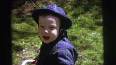 1972: a boy smiles in several settings while wearing various outfits and hats Stock Footage