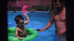 1972: father playing with his son in the pool with floating tube LYNBROOK Stock Footage