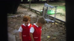 1972: two kids in similar dress is playing before a camera LYNBROOK, NEW YORK Stock Footage