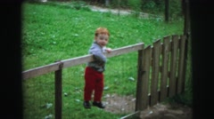 1972: the boy realise to open door at park even he tries to jump the fence Stock Footage