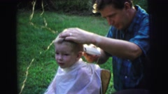 1972: the boy enjoys cute hair cut by his father at the garden LYNBROOK Stock Footage
