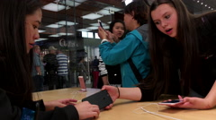 Young girls trying new released iPhone 7 and 7 plus inside Apple store Stock Footage