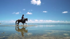 Cowboy man riding horse on shallow water at beach Stock Footage