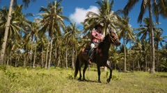 Cowboy man riding horse in circles on grass between palm trees close to beach Stock Footage