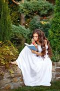 Girl with enthusiasm reads book Stock Photos