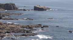 Multiple out croppings can be seen as waves surge in and out end of clip zoom Stock Footage