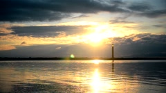Spectacular sunrise over water, with lighthouse Stock Footage