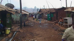 People walk down a dirty street in a shanty town. Stock Footage