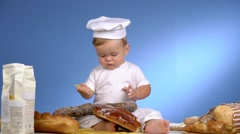 Child among bread on blue wall in cook hat Stock Footage