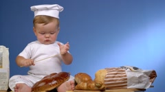 Baby baker on blue wall in cook hat Stock Footage