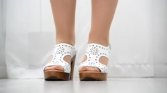 Female feet shod in white leather clogs Stock Footage