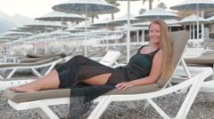 Beach woman enjoying the sea lying on the sun loungeron in the beach Stock Footage
