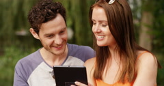 4k, young couple using a digital tablet together outside in a park. Slow motion. Stock Footage
