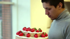 A man holds and cake bites Stock Footage