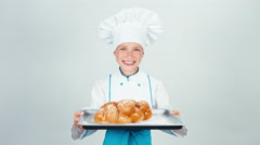 Portrait young baker holds oven-tray with braided bread and gives loaf you Stock Footage