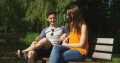 4k, A young couple chatting while sitting outside in a park. UK - October, 2016 Stock Footage
