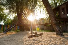 Playground with a hanging swing at sunset Kuvituskuvat