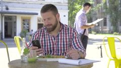 Young man browsing smartphone, during lunch. Stock Footage