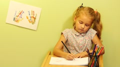 Cute girl draws family portrait. Stock Footage