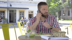 Young man talking by smartphone, during lunch, slider shot left. Stock Footage