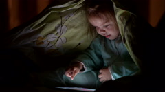 Little girl using tablet pc under blanket at night Stock Footage