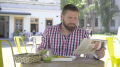 Young man eating lunch and reading newspaper, slider shot right Stock Footage