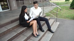 Young Beautiful Business Woman Female and Caucasian Male Use Documents, Laptop Stock Footage