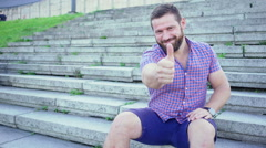 Young happy man sitting on stairs shows ok to camera, slider shot. Stock Footage