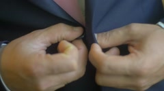 Groom in tuxedo looking at his cufflinks while fixing them Stock Footage