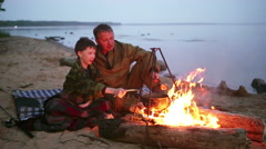 Father and son sitting around the campfire at the lake. Arkistovideo