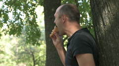 A young boy eating an ice cream cone near the tree Stock Footage