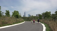 A family walking along a  path on on Governors Island, New York, United States. Stock Footage