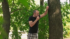 Young man eating ice cream near a tree in the Park Stock Footage