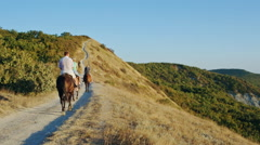 Group of people ride horses by gorgeous mountainside trail Stock Footage