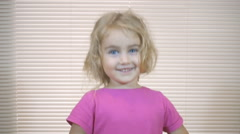 Little shaggy girl close-up, jumping and looking into the camera and smiling. Stock Footage