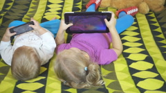 Small children using tablet pc on the bed at home. Brother and sister playing Stock Footage