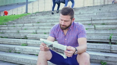 Young man sitting on stairs reading newspaper, slider and pan shot. Stock Footage