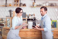 Two small business owners in aprons standing in cafe Stock Photos