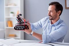Happy scientist observing his robot invention Stock Photos