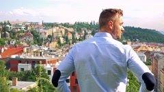 Young handsome business man looks at the city - shot on back - city (buildings)  Stock Footage