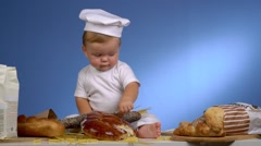 Baby baker playing with bread in cook hat Stock Footage