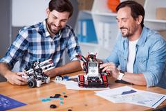 Joyful colleagues testing robots Stock Photos