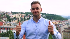 Young handsome business man shows thumbs up on agreement - city (buildings) Stock Footage