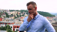 Young handsome business man thinks about something - city (buildings)  Stock Footage