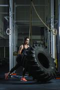 Powerful muscular woman CrossFit trainer doing tire workout at gym Kuvituskuvat