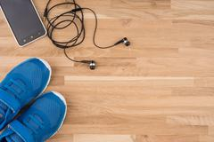 Flat lay shot of Sport equipment. Sneakers, earphones and phone on wooden bac Stock Photos