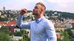 Young handsome business man rejoices - city (buildings) in background Stock Footage