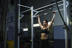 Powerful attractive woman CrossFit trainer do pull ups during workout Kuvituskuvat