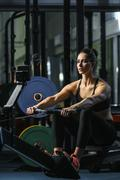 Attractive muscular woman CrossFit trainer do workout on indoor rower Kuvituskuvat